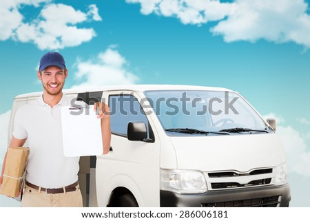 Happy delivery man holding cardboard box and clipboard against blue sky - stock photo
