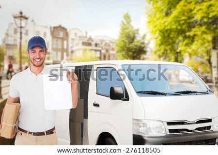 Happy delivery man holding cardboard box and clipboard against bridge in amsterdam - stock photo