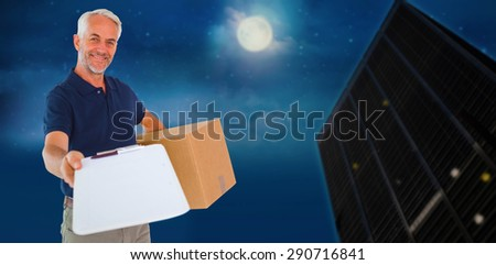 Happy delivery man holding cardboard box and clipboard against city at night - stock photo