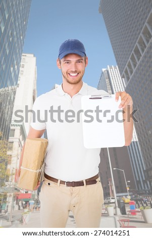 Happy delivery man holding cardboard box and clipboard against new york - stock photo