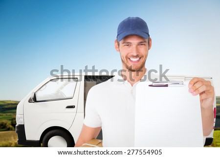 Happy delivery man holding cardboard box and clipboard against scenic landscape - stock photo