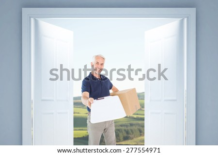 Happy delivery man holding cardboard box and clipboard against scenic landscape