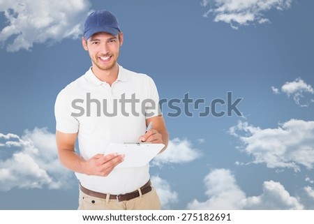 Happy delivery man holding clipboard against blue sky - stock photo