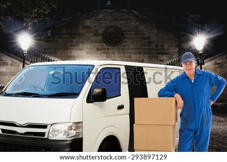Happy delivery man leaning on pile of cardboard boxes against building by night - stock photo