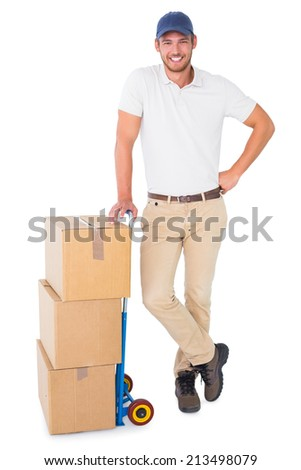 Happy delivery man leaning on trolley of boxes on white background - stock photo