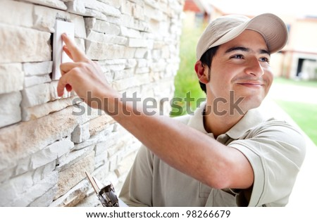 Happy delivery man outdoors ringing house doorbell - stock photo