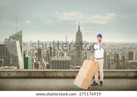 Happy delivery man pushing trolley of boxes against cityscape