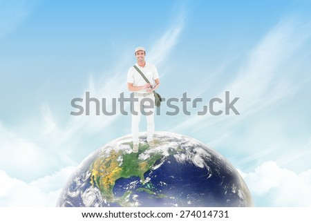 Happy delivery man using digital tablet against blue sky