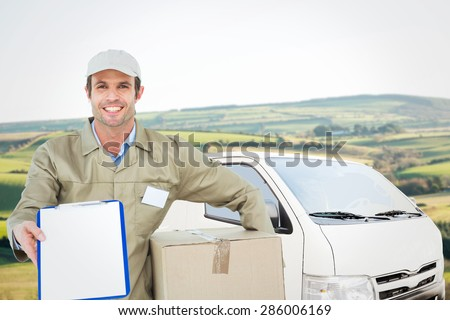 Happy delivery man with box showing clipboard against scenic landscape - stock photo