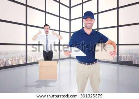 Happy delivery man with cardboard box and clipboard against room with large window showing city - stock photo
