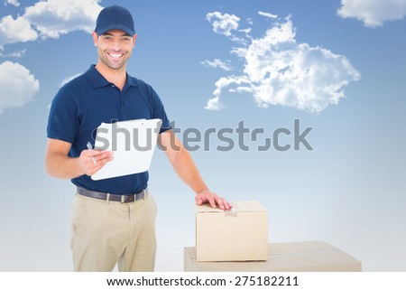 Happy delivery man with cardboard boxes and clipboard against blue sky - stock photo