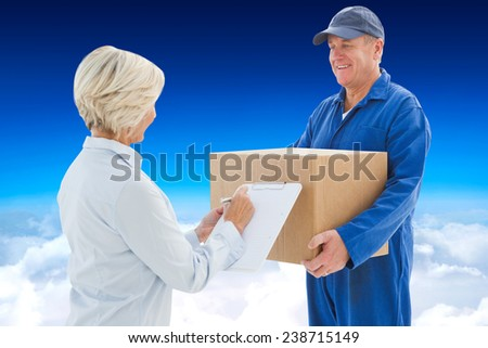 Happy delivery man with customer against blue sky over clouds - stock photo
