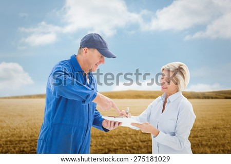 Happy delivery man with customer against bright brown landscape - stock photo