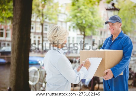 Happy delivery man with customer against canal in amsterdam - stock photo