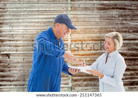 Happy delivery man with customer against wooden planks - stock photo
