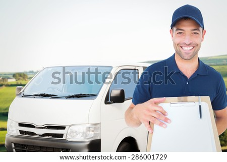 Happy delivery man with package and clipboard against scenic landscape - stock photo