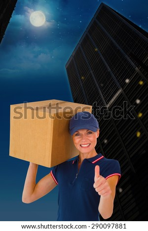Happy delivery woman holding cardboard box showing thumbs up against city at night - stock photo