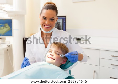 happy dentist consulting little patient in office - stock photo