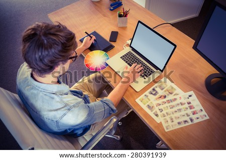 Happy designer working on his laptop in creative office - stock photo