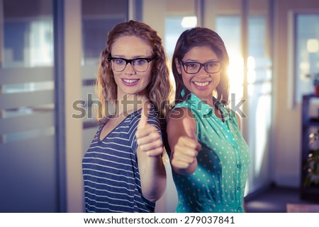 Happy designers showing thumbs up in creative office - stock photo
