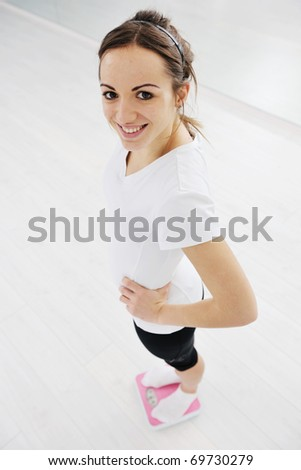 happy diet concept with young woman on pink scale at sport fitness gym club - stock photo