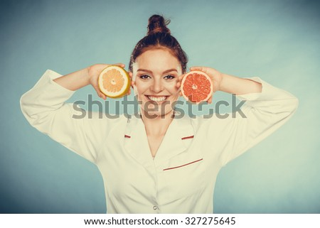 Happy dietitian nutritionist holding grapefruit having fun. Woman promoting healthy food fruit. Right eating nutrition and slimming concept. Instagram filter. - stock photo