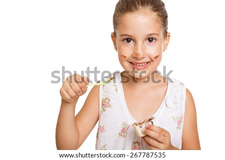 Happy dirty and messy little girl eating cocoa cream smiling looking at camera holding a cream package and spoon isolated on white background. Horizontal, copy space, mild retouch. - stock photo