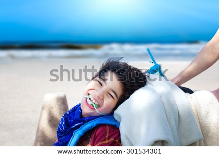 Happy disabled boy being pushed in wheelchair, smiling,  with ocean beach in background - stock photo