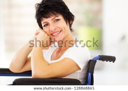 happy disabled middle aged woman sitting on wheelchair - stock photo