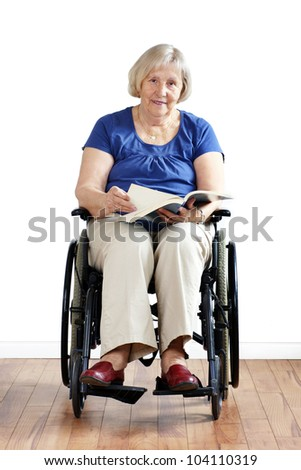 Happy disabled or handicapped senior woman in wheelchair, reading a book, looking at camera. - stock photo