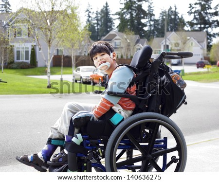 Happy disabled six year old boy waiting on sidewalk in wheelchair. Child has cerebral palsy - stock photo