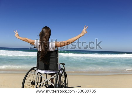 happy disabled woman in wheelchair outdoors beach showing victory sign - stock photo