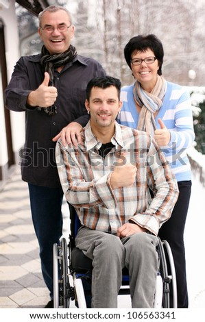 Happy disabled young man with palsy in wheelchair surrounded by father and mother, laughing
