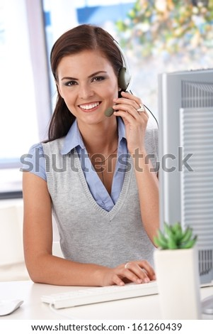 Happy dispatcher working at desk in bright office, looking at camera. - stock photo