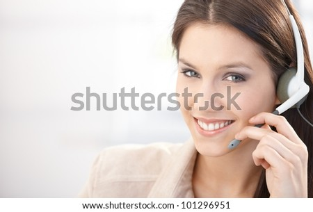 Happy dispatcher working in call center, using headset, smiling. - stock photo