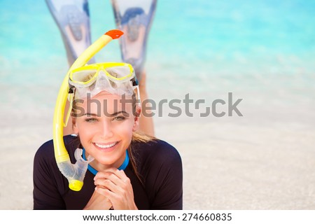 Happy diver woman lying down on the beach, wearing flippers and snorkeling mask, having fun on beach resort, enjoy water sport and active summer vacation - stock photo