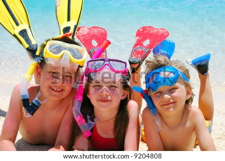 Happy Divers on a Beach - stock photo