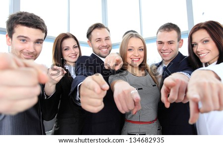 Happy diverse group of executives all pointing at you