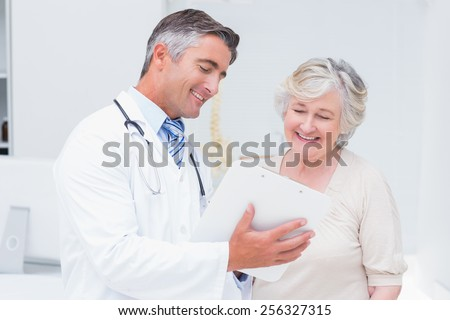 Happy doctor and patient discussing over reports in clinic - stock photo