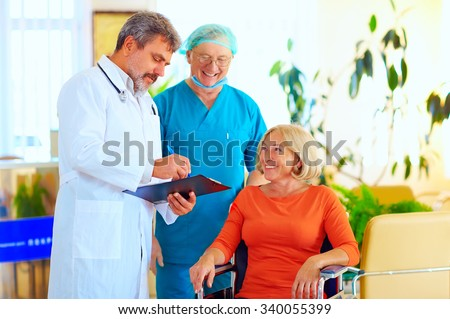 happy doctor and surgeon consulting patient about treatment before discharging from hospital - stock photo