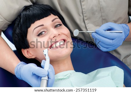 Happy doctor drills bad teeth of the patient. Dentist makes the process of treatment of a beautiful young girl. The patient smiles and sits in the chair at the dentist - stock photo