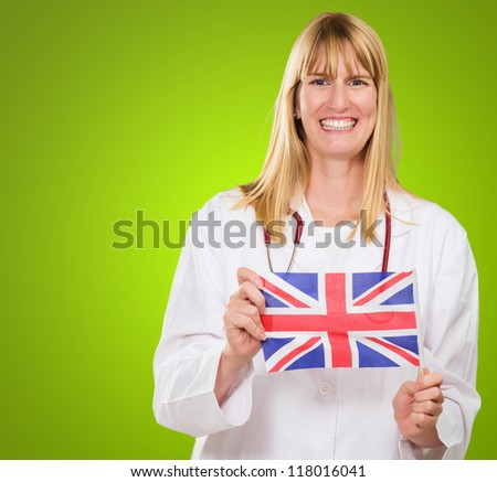 Happy Doctor Holding British Flag against a green background