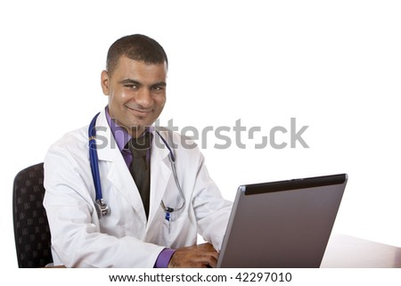 Happy doctor is sitting on his desk and typing on laptop. Isolated on white.