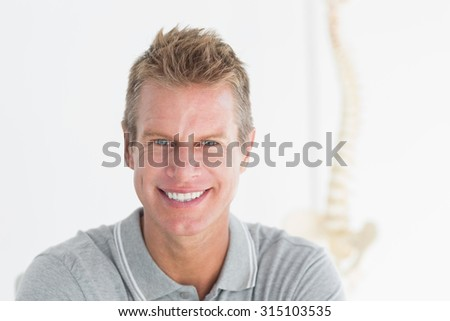 Happy doctor looking at camera in medical office - stock photo