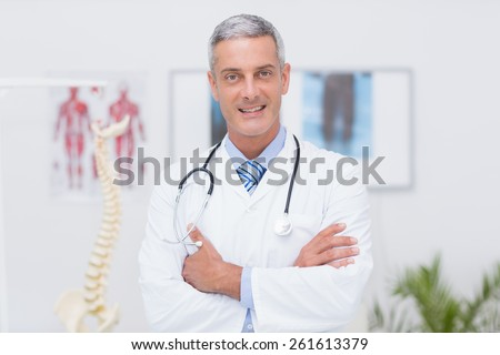 Happy doctor looking at camera with arms crossed in medical office - stock photo