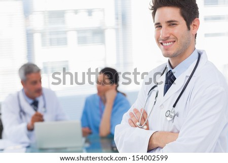 Happy doctor looking at camera with colleagues behind in medical office - stock photo