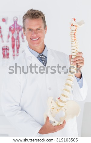 Happy doctor showing anatomical spine in clinic - stock photo