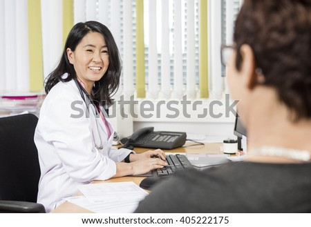 Happy Doctor Using Computer While Looking At Patient At Desk - stock photo