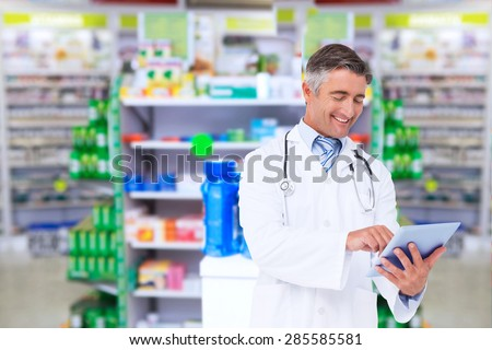 Happy doctor using tablet pc against close up of shelves of drugs - stock photo