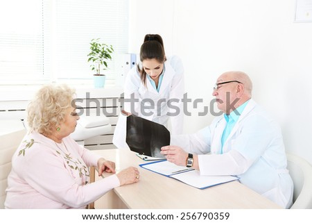 Happy doctors and patient in hospital clinic - stock photo